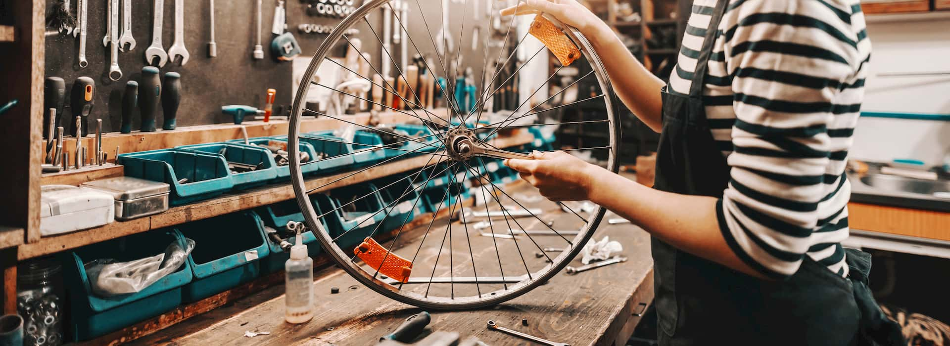 Cute Caucasian female worker holding and repairing bicycle wheel while standing in bicycle workshop. © Adobe Stock